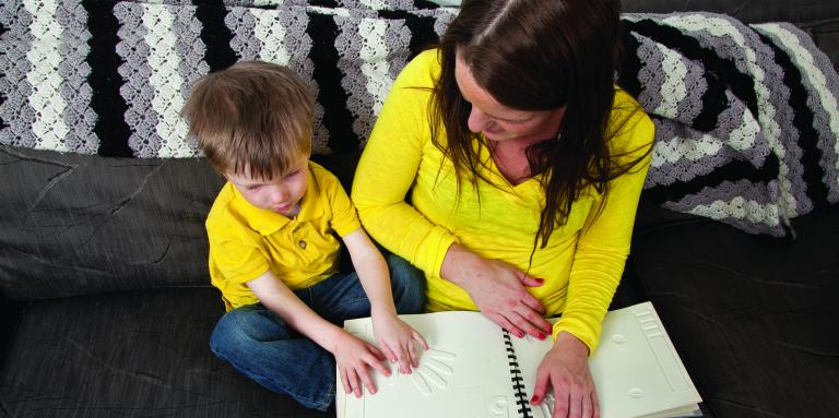 A young boy and his mom, both wearing yellow shirts, are going through a tactile book while sitting on a couch.