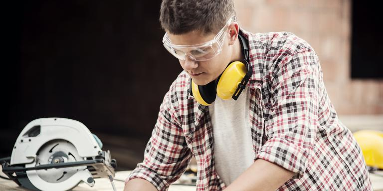 Man looking down and marking a piece of wood with a pencil. He is wearing protective glasses.