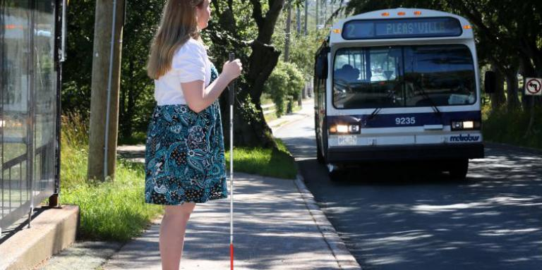 Woman with a white cane waiting for the bus