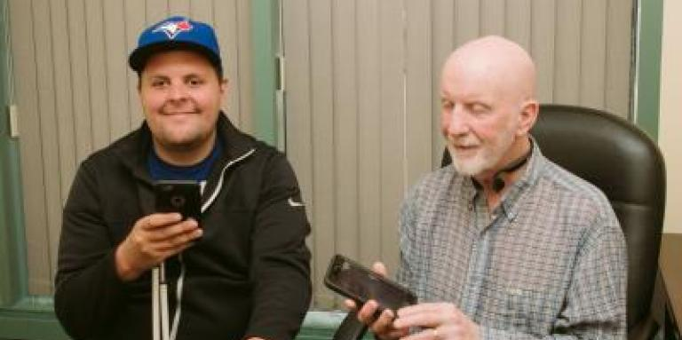 Two men smile and hold iPhones.