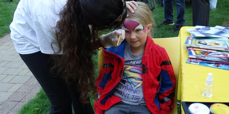 A young girl sits and has her face painted by a volunteer.
