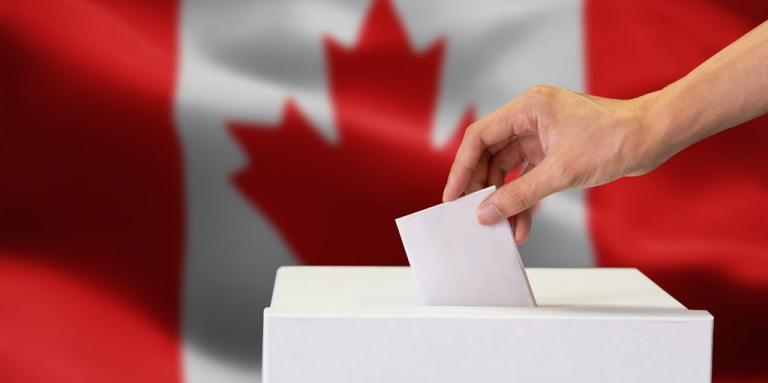 A hand dropping a ballot into a box; the Canadian flag in the background.