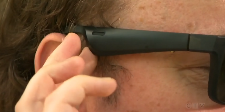 A man touches his Bose eyeglass frames to adjust the directional audio.