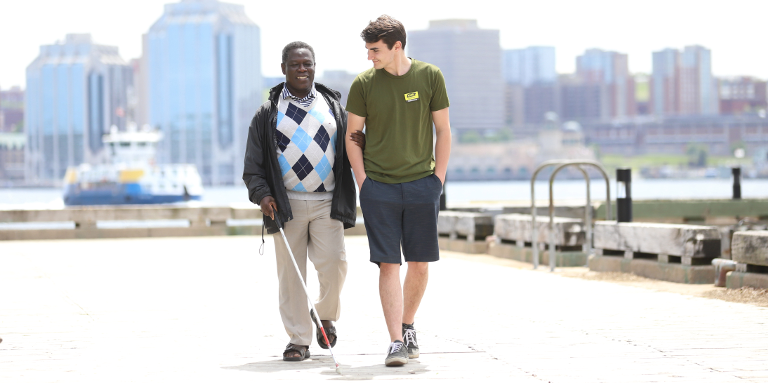 A man using a white cane walks with a sighted volunteer along a boardwalk on a sunny day.