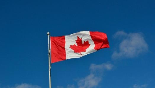 A Canadian flag waves in a clear, blue sky.